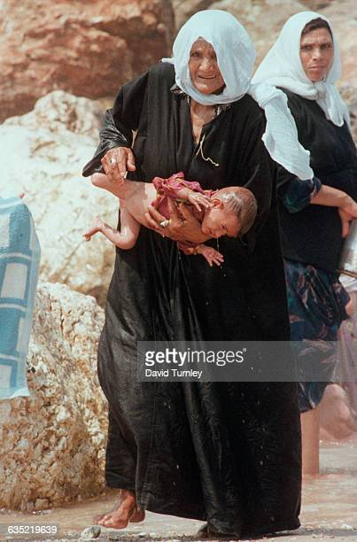 Palestinian woman living in a refugee camp in Gaza holds her dripping infant granddaughter, who struggles and squirms after an unwanted bath.