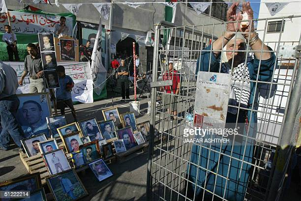 Palestinian woman locks herself in a symbolic jail as pictures of prisoners are displayed during a demonstration in solidarity with Palestinian...
