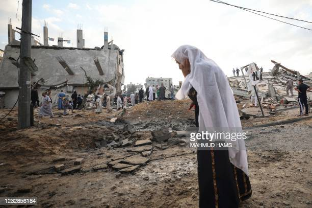 Palestinian woman looks at destroyed buildings on the first day of the Eid al-Fitr holiday, which marks the end of the Muslim fasting month of...