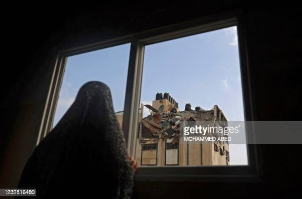 Palestinian woman looks at the rooftop of a building which was hit by an Israeli airstrike at al-Shati Refugee Camp in Gaza City, early on May 11,...