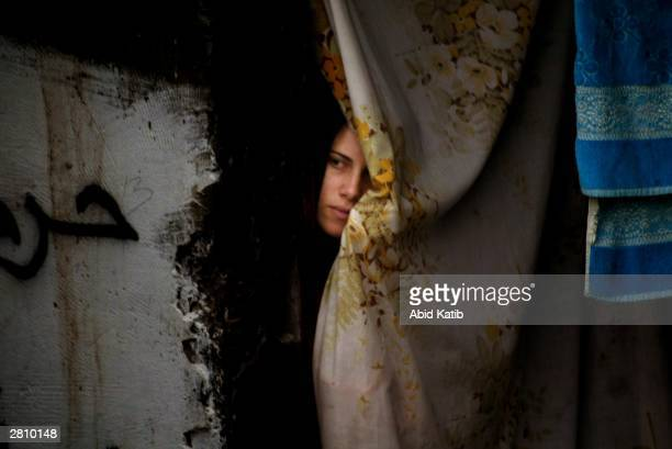 Palestinian woman looks at the supporters of the Islamic Hamas movement as they attend a demonstration in the southern Gaza Strip refugee camp of...