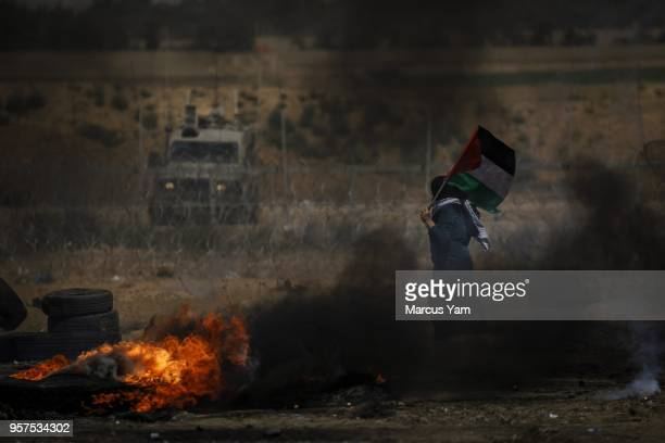 Palestinian woman marches around with the Palestinian flag in front of Israeli soldiers standing guard during a the recurring Great March of Return...