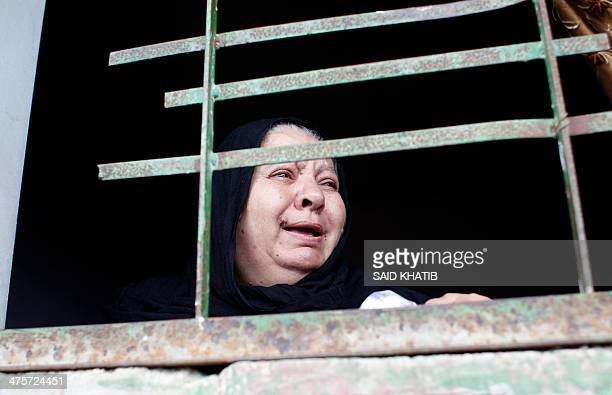 A Palestinian woman mourns as she looks out of a window of a house in the town of Khan Younis in the southern Gaza Strip during the funeral...