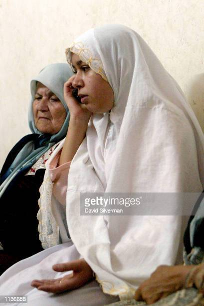 Palestinian woman Nasreen Ajuri speaks on a mobile phone alongside her motherinlaw Rashida Ajuri as they take refuge in a relative's home July 21...