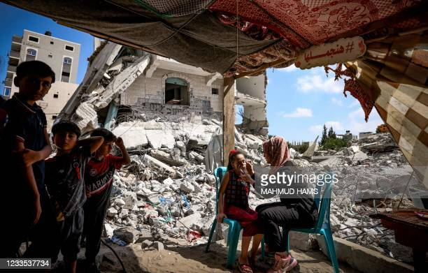 Palestinian woman paints a national flag on the face of a child, amidst the rubble of buildings destroyed by last month's Israeli bombardment of the...