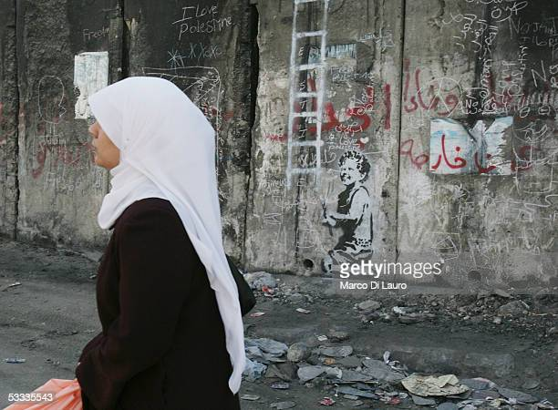 Palestinian woman passes by a graffiti entitled Escapism made by the British guerrilla graffiti artist Banksy is seen on August 6 2005 on Israel's...