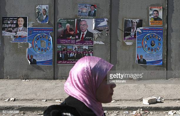Palestinian woman passes parliamentary election campaign posters on Israel's separation wall near the Israeli army's Qalandia checkpoint between...