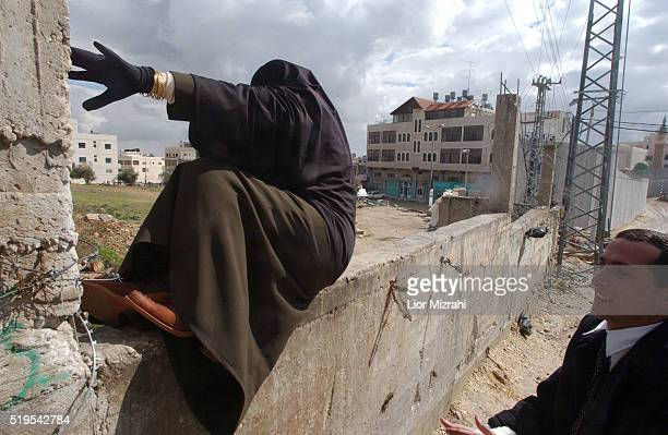 A Palestinian woman passes the concrete wall separating east Jerusalem from the West Bank village of Abu Dis Sunday Feb 02 2003 Israel has asked the...