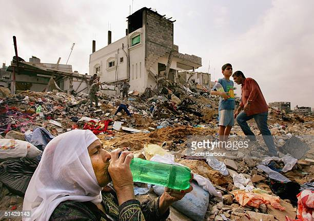 Palestinian woman pauses to drink some water while searching for her belongings October 6 2004 in the debris of several homes destroyed by Israeli...