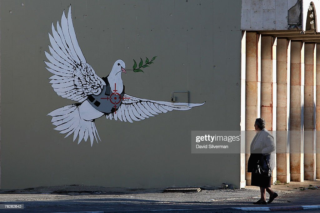 A Palestinian woman pauses to look at a wall painting by elusive British graffiti artist Banksy December 5, 2007 on a shop wall in the biblical city of Bethlehem in the West Bank. The Bristol-born artist has adorned Israel's West Bank separation barrier and Bethlehem walls with new images, including this one of a dove wearing a flak jacket and a soldier being frisked by a young girl. His works, along with those of other international artists, are part of an exhibition called Santa's Ghetto.