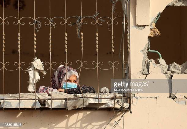 Palestinian woman peeks from the window of her home, hit by Israeli bombardment in Gaza City, after a ceasefire brokered by Egypt between Israel and...