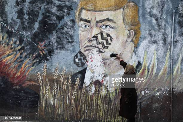 Palestinian woman places a shoe a graffiti painted by Palestinians protesters showing US President Donald Trump with a footprint on his face in a...
