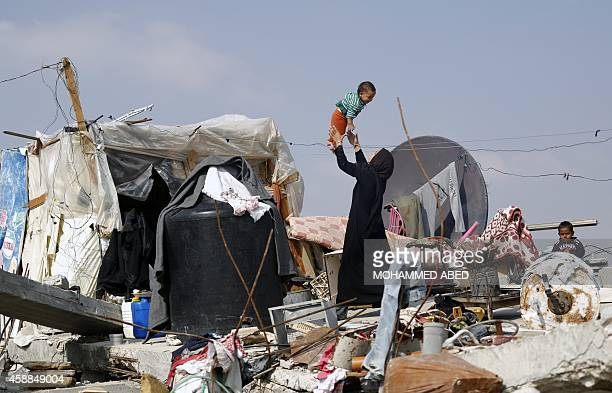 Palestinian woman plays with her child on the rubble of their family's home which was destroyed during the 50-day Gaza war between Israel and...