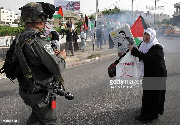 A Palestinian woman points at a portrait of a loved one detained in an Israeli jail in front of a member of the Israeli security forces during a...