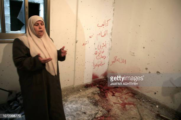 Palestinian woman prays in a shrapnelriddled room with blood stains and a slogan written in Arabic Ashraf Naalwa your blood awaits a victory after...