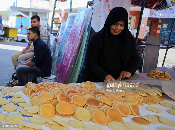 Palestinian woman prepares traditional pancakes known as ''Qatayef'' in a street market on the fifth day of the holy month of Ramadan in Rafah in the...