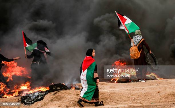 A Palestinian woman protesters carry and wear Palestinian flags as they stand amidst smoke from burning tyres during clashes following a...