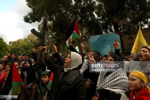 A Palestinian woman raises a rifle as others chant slogans during a demonstartion in the Rashidiyah camp near Lebanon's southern port city of Tyre to...