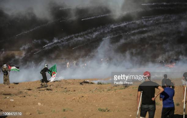 Palestinian woman raising the Algerian flag while Israeli troops are firing tear gas bombs toward them the eastern borders in Gaza