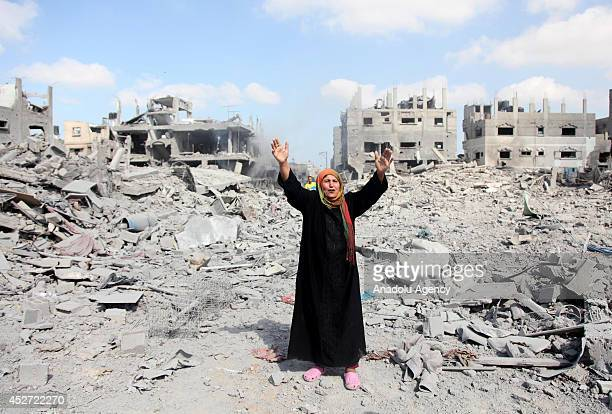 Palestinian woman reacts as Palestinians try to find their belongings inside the debris of the buildings during a 12hour humanitarian truce in Beit...