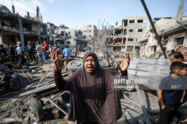 Palestinian woman reacts as she and Palestinians search their belongings while rescue efforts continue to evacuate Palestinians from the rubble of...