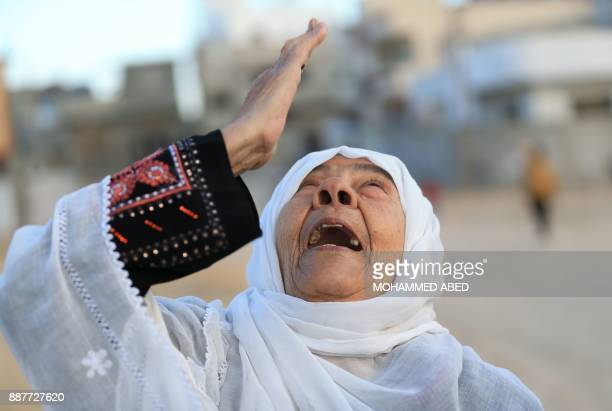 Palestinian woman reacts on a street in Beit Hanun in the northern Gaza Strip on December 7 a people gather during a Hamas rally against US President...