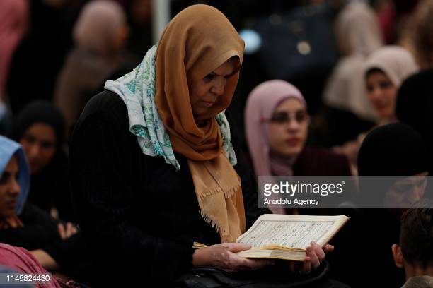 Palestinian woman reads Qur'an during the third Friday Prayer of holy fasting month of Ramadan at AlAqsa Mosque compound in Jerusalem on May 24 2019