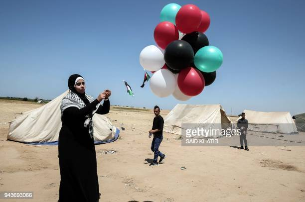 Palestinian woman releases ballons into the air at the site of a tent protest on April 9 on the IsraelGaza border east of Rafah in the southern Gaza...