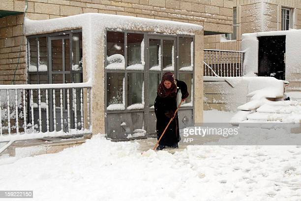 A Palestinian woman removes snow in front of a building after heavy snow falls on January 10 2013 in Tuqua near the West Bank City of Bethlehem...