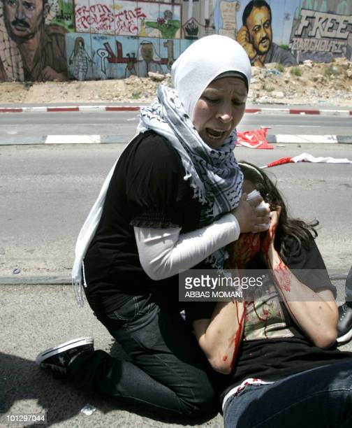 A Palestinian woman screams as she helps a US peace acitivist wounded in the eye by a tear gas grenade thrown by Israeli soldiers to disperse...