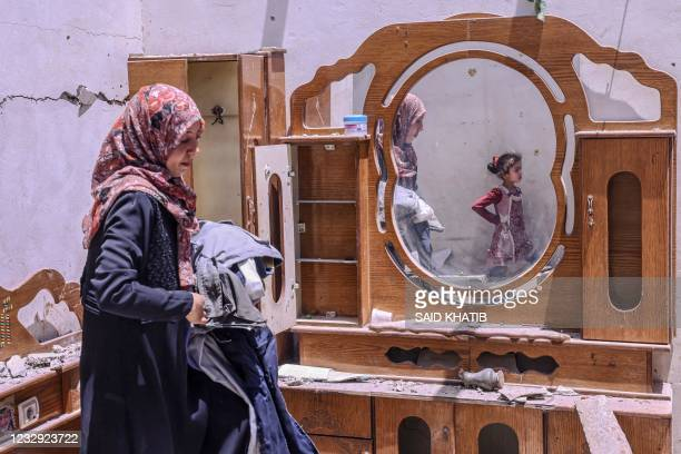 Palestinian woman searches for the families belongings at their house, after it was destroyed by an Israeli airstrike, in the city of Rafah, in the...