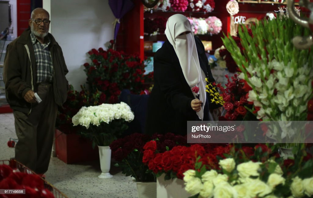 A Palestinian woman seller prepares flowers at a flower shop on the eve of Valentine's Day in Gaza City , 13 February 2018.