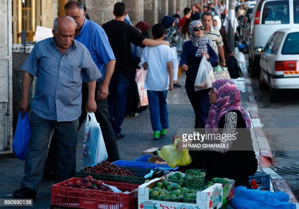 A Palestinian woman sells fruit on the street in east Jerusalem on May 31 2017 Fifty years after Israel seized east Jerusalem in the 1967 SixDay War...