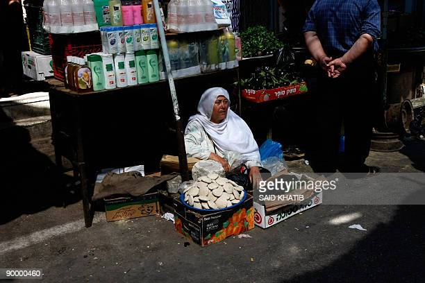 A Palestinian woman sells goods at a popular market in Rafah in the southern Gaza Strip on the first day of the Muslim fasting month of Ramadan on...