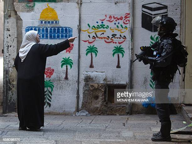 A Palestinian woman shouts at Israeli policemen in the old city of Jerusalem on October 30 2014 after Israeli authorities temporarily closed the...