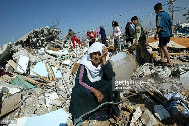 Palestinian woman sits next to her destroyed house after it was demolished by Israeli bulldozers May 19 2003 at Beit Hanoun town in the northern Gaza...