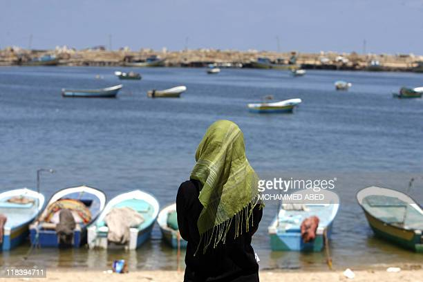 A Palestinian woman stands along the dock in the port at Gaza City on July 5 as proPalestinian activists from an international flotilla banned from...