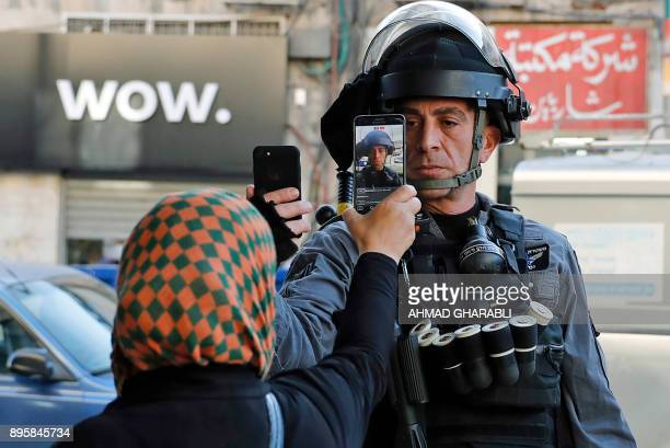 Palestinian woman takes a picture of a member of the Israeli security forces as he takes her picture in a street in Jerusalem on December 16 as...