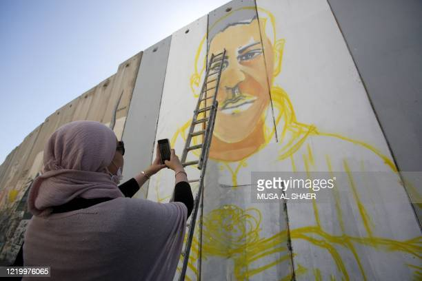 Palestinian woman takes a picture of a mural of Iyad Hallak, a 32-year-old autistic Palestinian man shot dead by Israeli police, painted by...