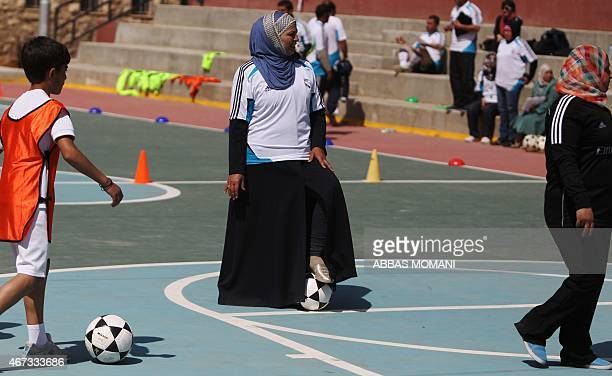 Palestinian woman takes part in a football training session given by Spanish club Real Madrid in the West Bank city of Ramallah on March 23, 2015 as...