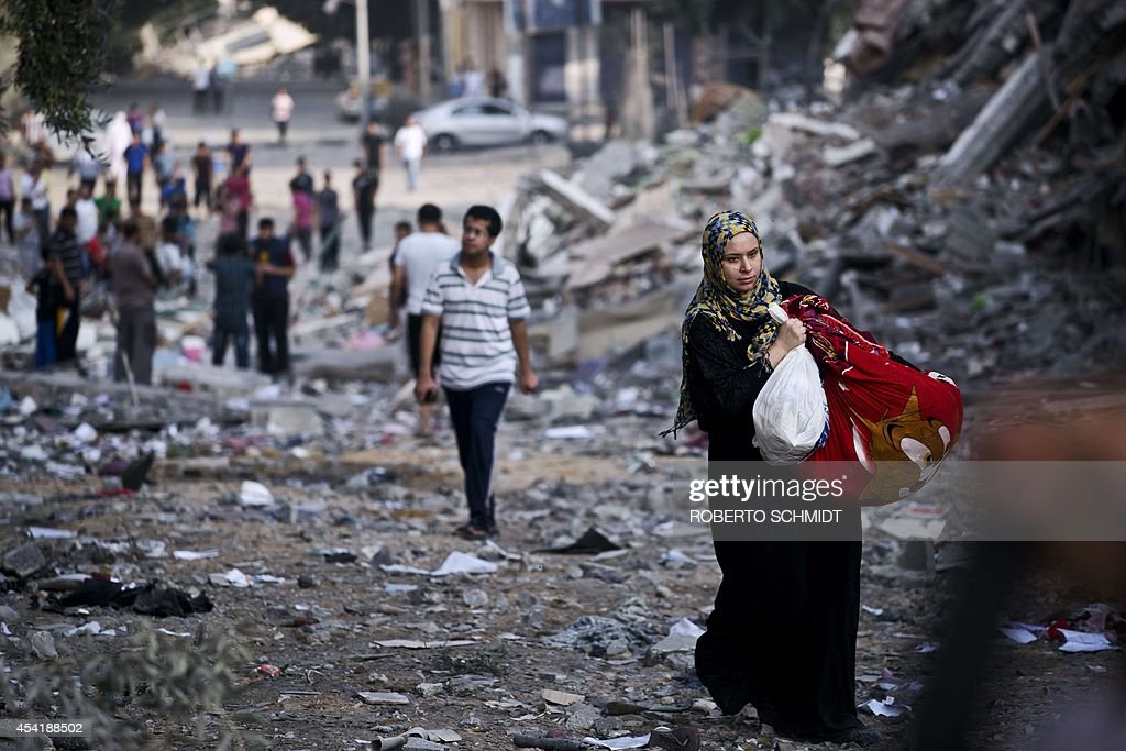 A Palestinian woman takes some of their belongings from her partially destroyed home across the street from where a high rise apartment building in Gaza City was targeted by Israeli air strikes overnight on August 26, 2014. The residents of the tower were warned to leave the building before the bombing took place. The UN estimates that about a quarter of the 1.8 million inhabitants of Gaza have been displaced by fighting between Hamas militants and Israel.