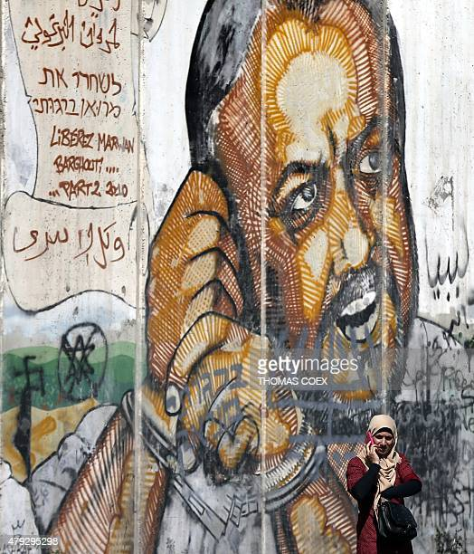 A Palestinian woman talks on the phone in front of graffiti depicting of jailed Palestinian Fatah movement leader Marwan Barghuti at the Qalandia...