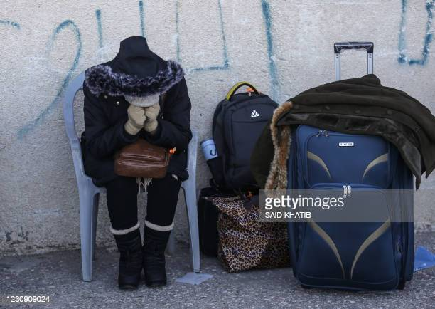 Palestinian woman waits by her luggage at the Rafah border crossing departure area to travel from the Gaza Strip into Egypt, on February 1 after the...