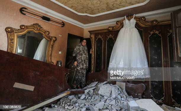 Palestinian woman walkes into a room damaged by an Israeli airstrike earlier this week in the Gaza Strip on November 14 2018 A ceasefire held today...
