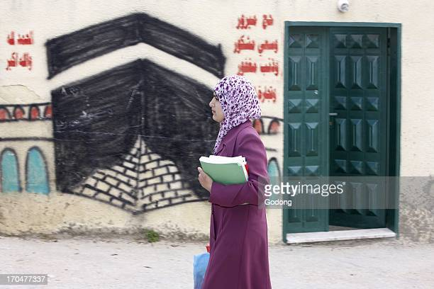Palestinian woman walking past a wall painting depicting the Kaaba Balah Occupied Palestinian Territory