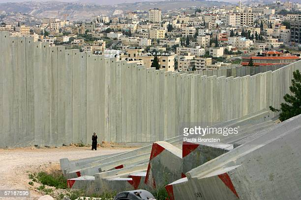 Palestinian woman walks along the wall on March 26, 2006 bordering Abu Dis, West Bank and East Jerusalem, Israel. The controversial separation...