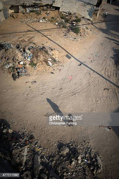 A palestinian woman walks among the dust and rubble of bombed homes that still wait to be demolished or rebuilt on June 15 Gaza City Gaza The...