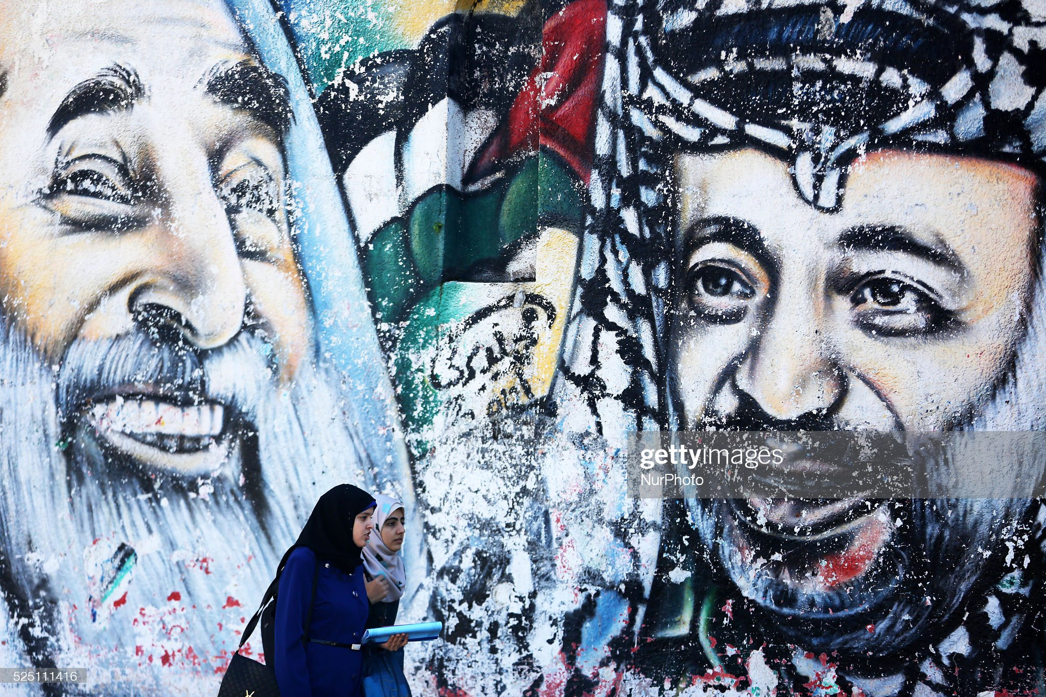 A Palestinian woman walks next to a graffiti of Palestinian late leader Yasser Arafat : News Photo