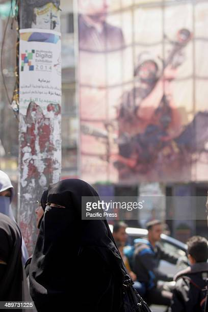"""Palestinian woman walks next to a wall drawing of a militant carrying a rocket in Rafah in the southern Gaza Strip. Nakba, or """"catastrophe"""", marks..."""