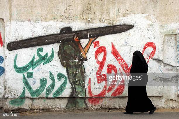 "Palestinian woman walks next to a wall drawing/mural of a militant carrying a rocket in Rafah in the southern Gaza Strip. Nakba, or ""catastrophe"",..."